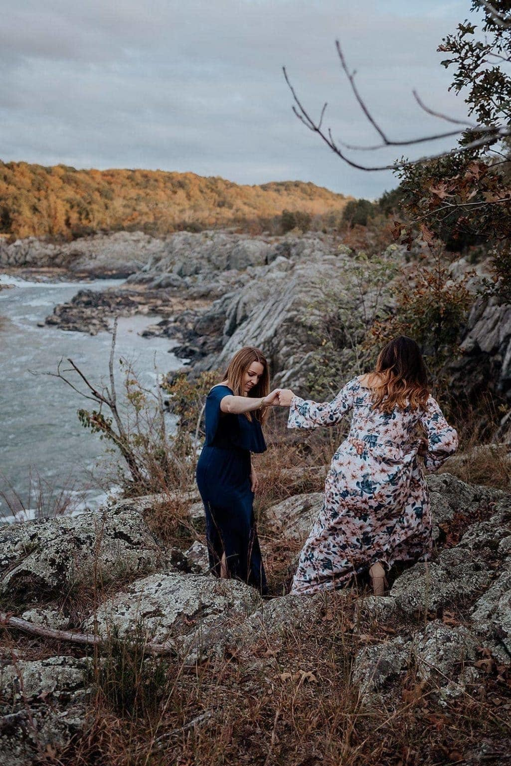 A woman helps her partner climb down a rocky slope at Great Falls Park