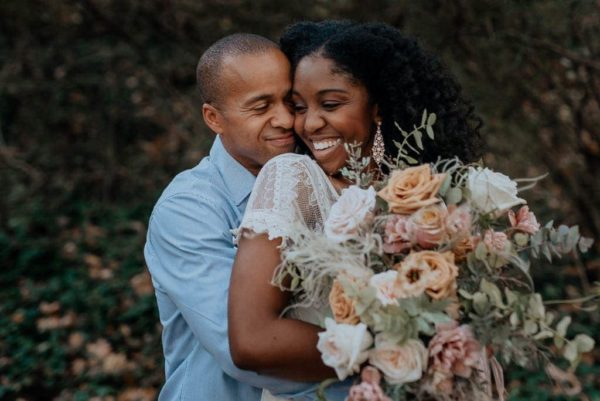 A newlywed couple embraces with a gorgeous wedding bouquet in the foreground