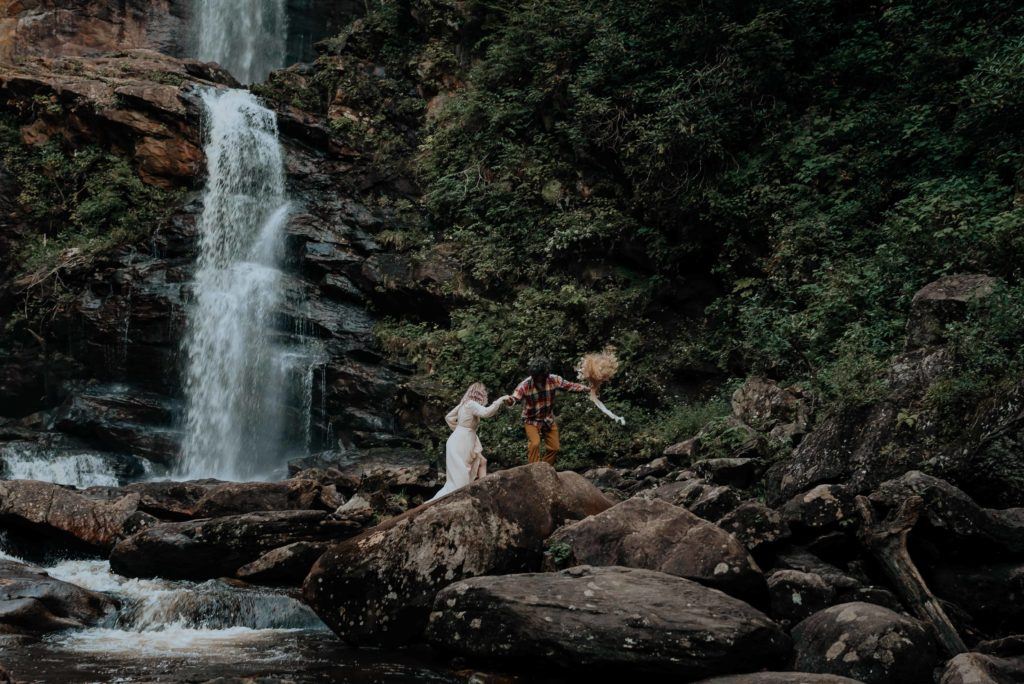 A newly-eloped couple scrambles across some large rocks at the base of an epic waterfall. Photographed by virginia elopement photographer, Flit Photography