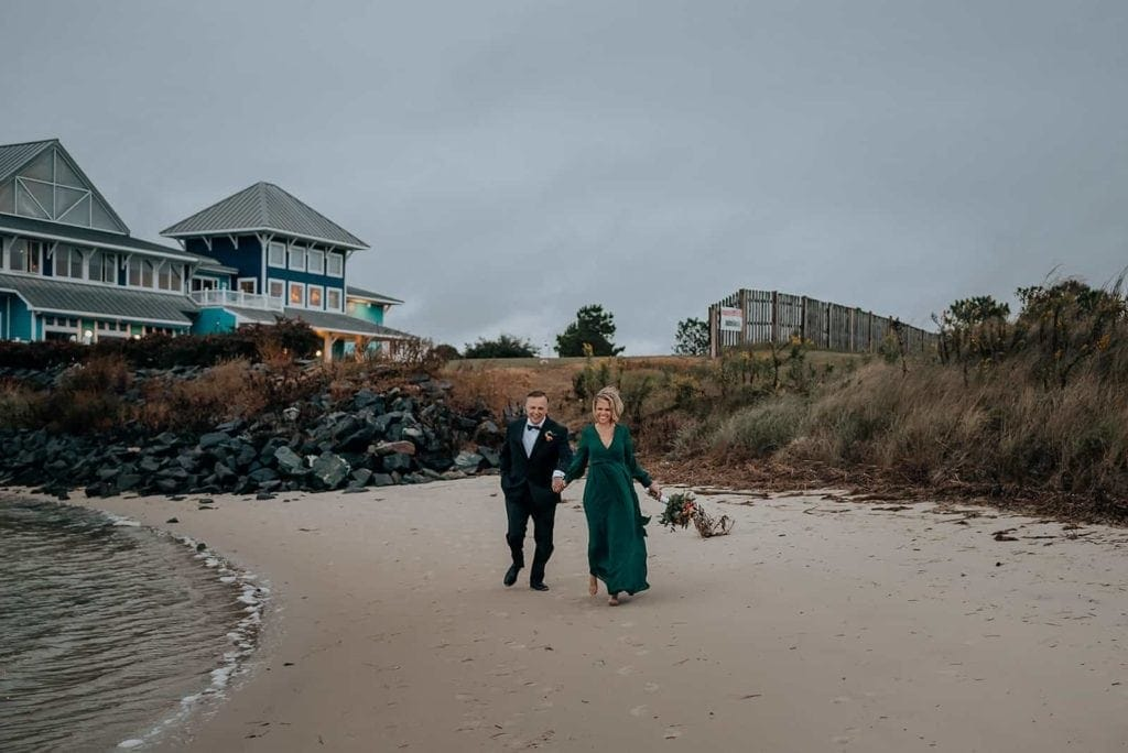 A middle-aged couple runs down a beach on the coast of virginia after eloping. photographed by virginia elopement photographer, Flit Photography