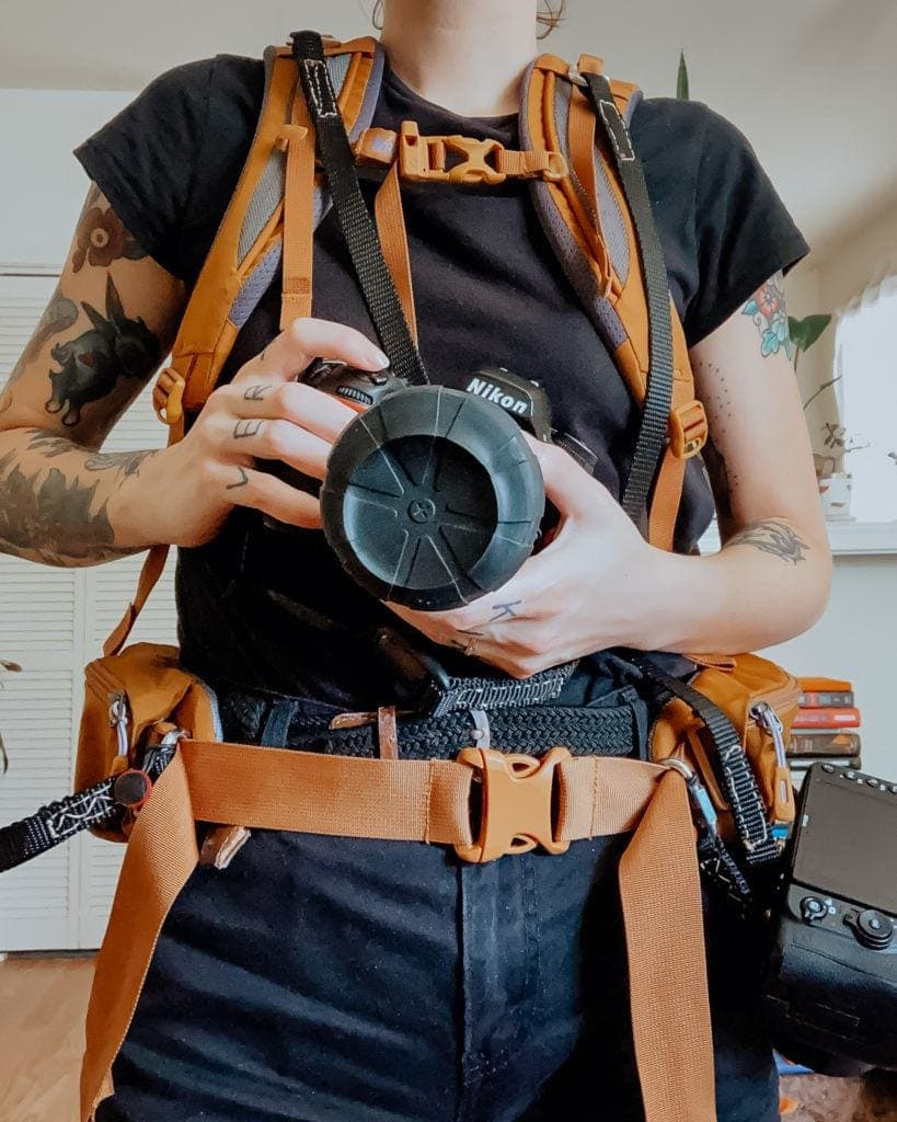 A photographer in a custom photography strap and hiking pack.