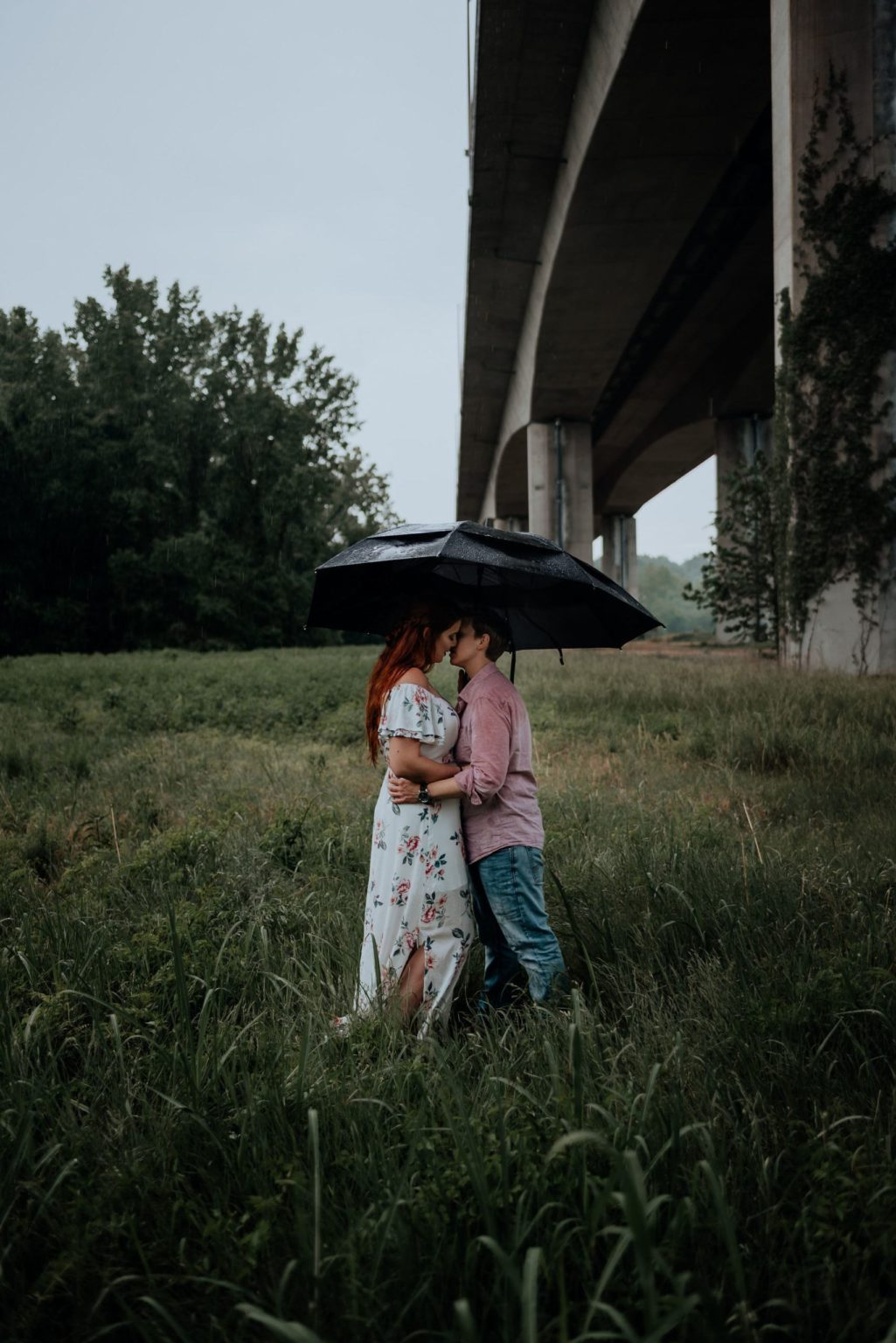 A lesbian couple kisses under a black umbrella in the middle of a field on belle isle in the middle of a rain storm.