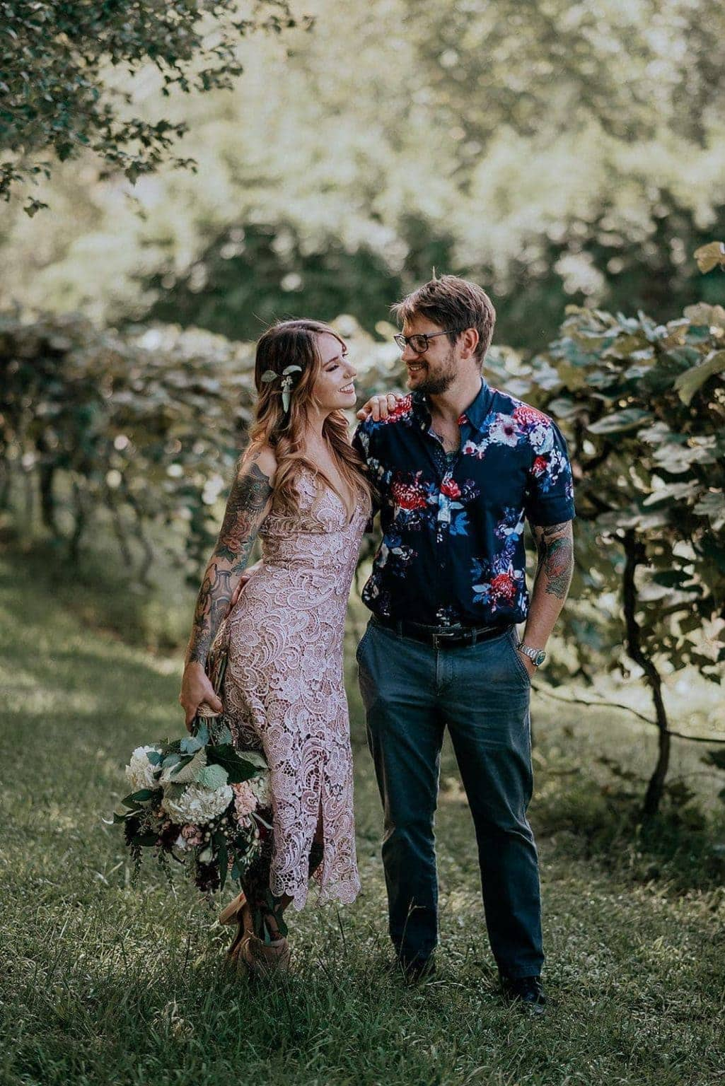 A newly-eloped couple embraces in a vineyard