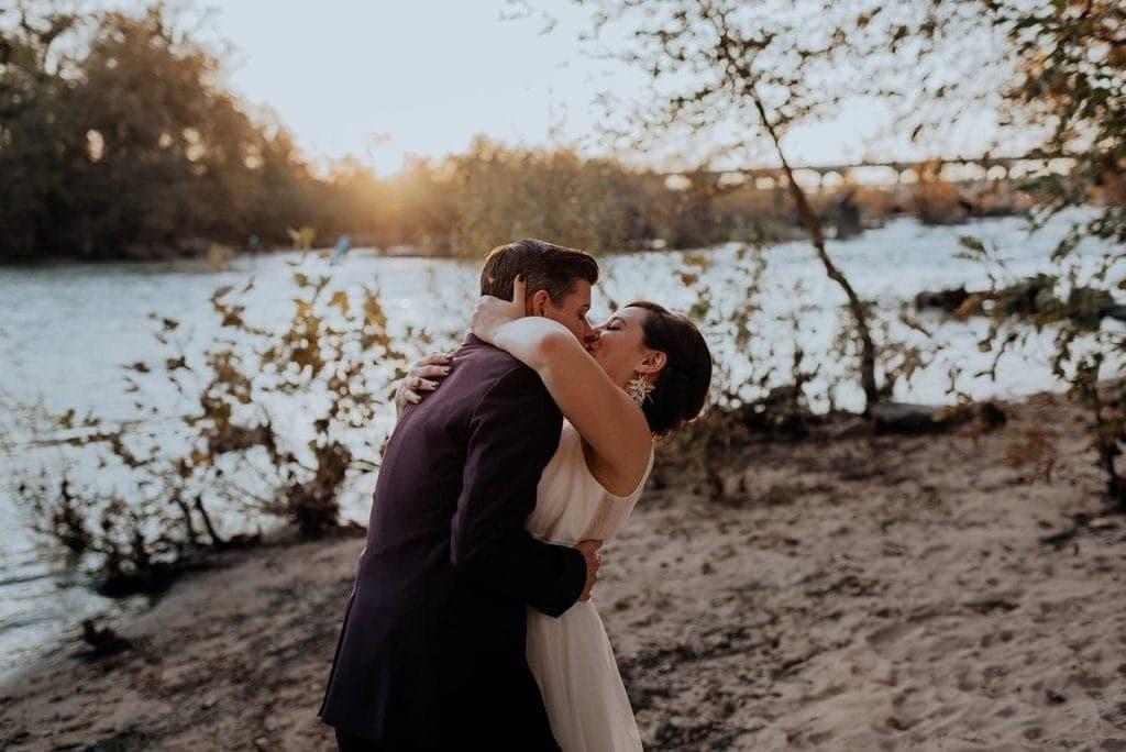A newly-eloped lesbian couple kiss each other on a beach