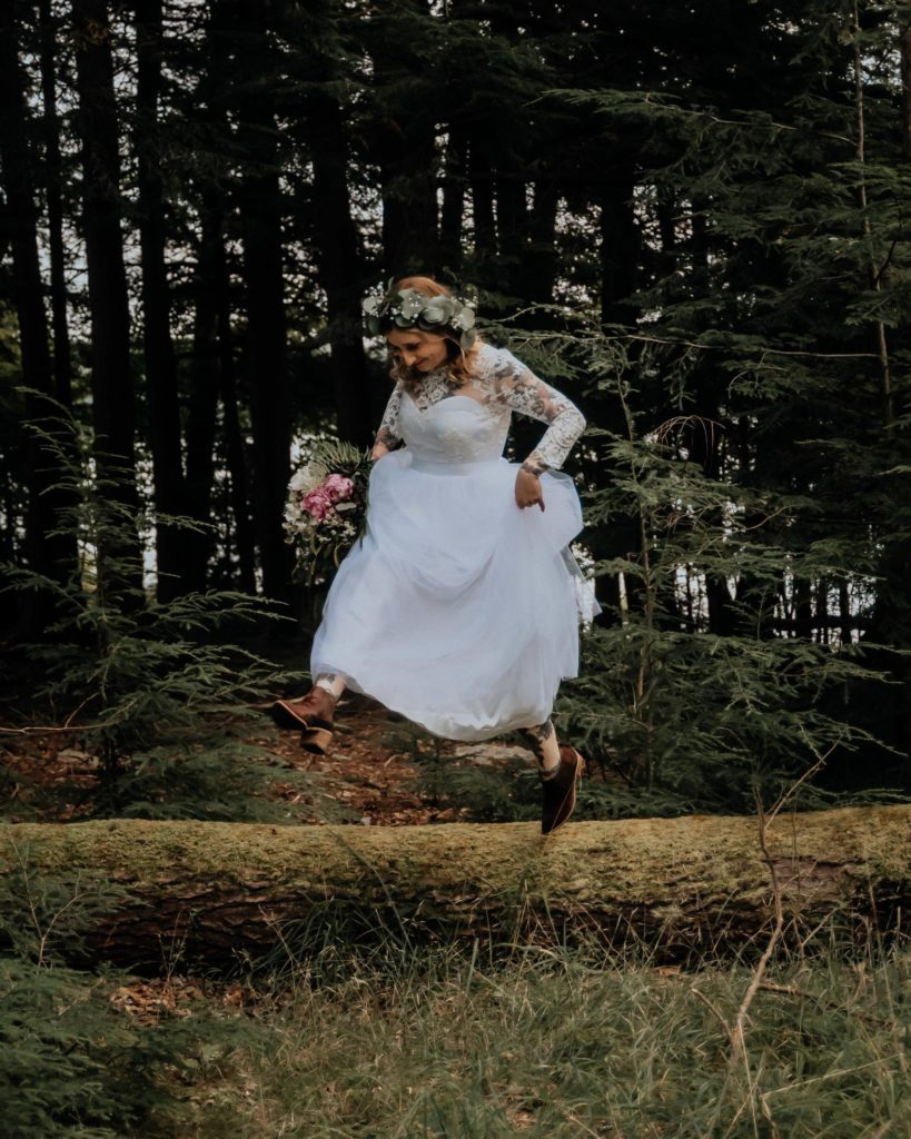 An eloping bride leaps from a log.