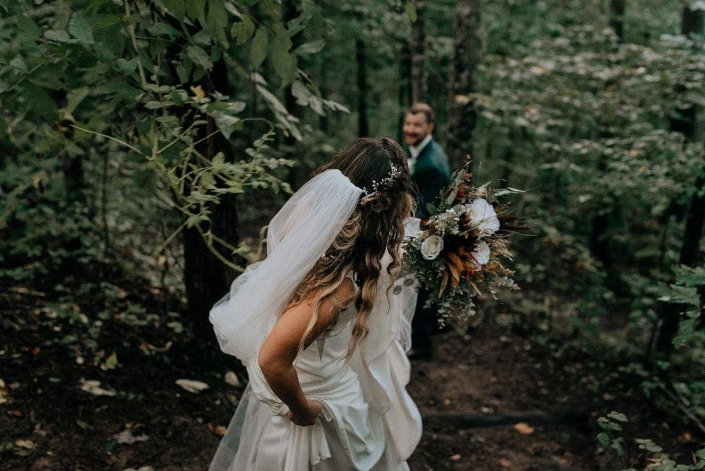 An eloping couple hikes through the woods. The bride is in the foreground in a white dress and veil
