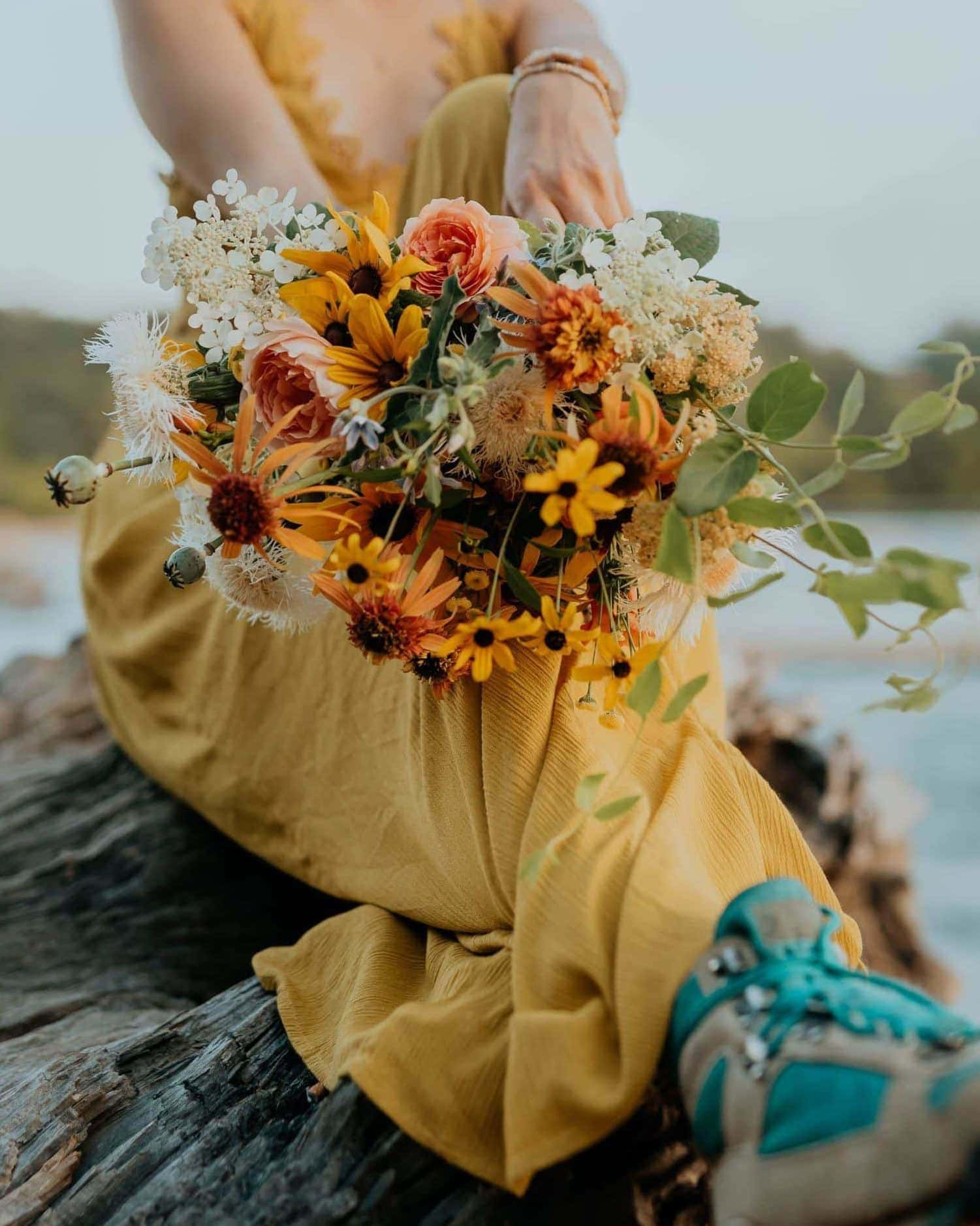 A bride in a yellow dress and vintage hiking boots shows off her bouquet.Photographed by virginia elopement photographer, Flit Photography.