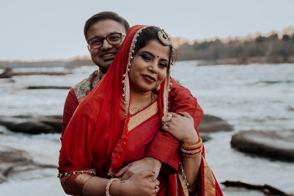 An Indian couple in traditional wedding outfits embraces on a rock in the James River at sunset after their elopement ceremony.