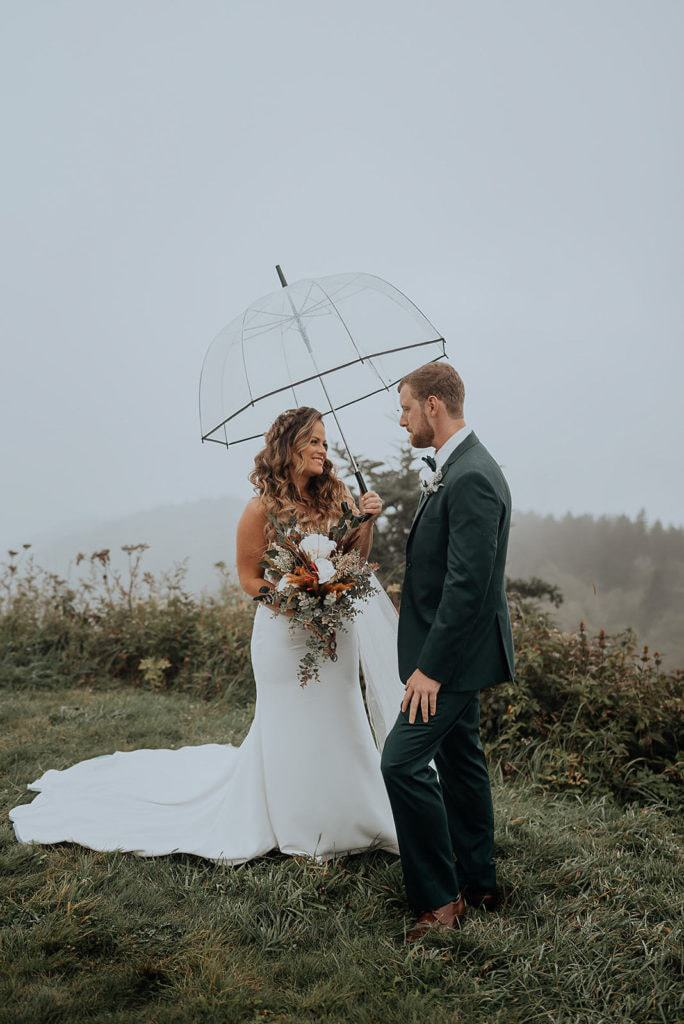An eloping couple stands on a foggy mountaintop in the mountains outside Asheville NC