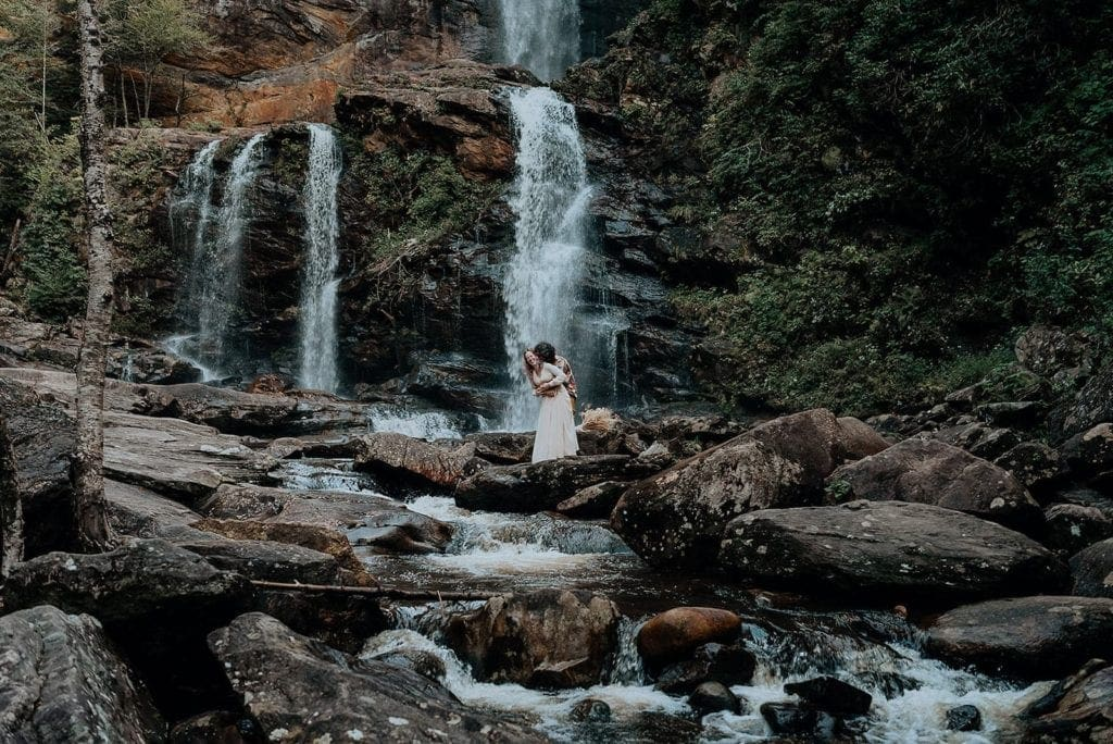 An eloping couple laughs together in front of a large waterfall in North Carolina