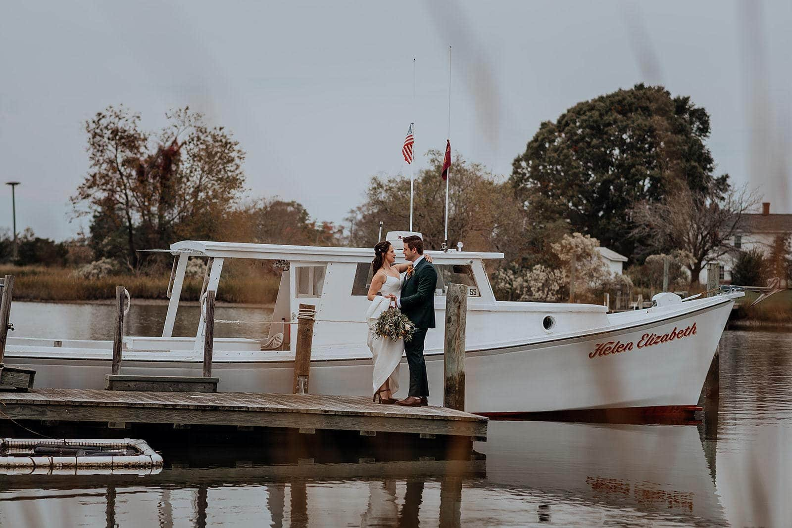 An eloping couple embraces on a dock at the inn at Tabb's Creek along the Chesapeake Bay.