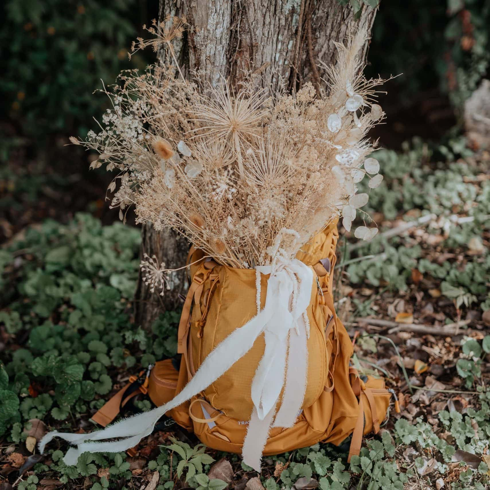 A bouquet of dried flowers and grasses is secured in a gold-colored hiking backpack for an elopement. Photographed by virginia elopement photographer, Flit Photography